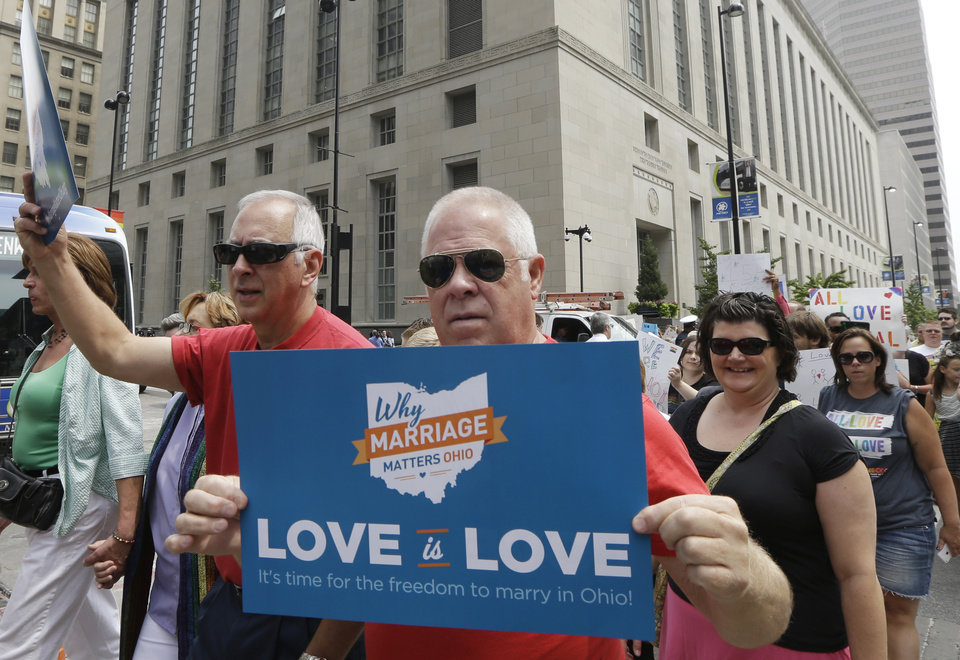 Photo - Gay marriage supporters march from the Potter Stewart United States Courthouse, rear, Wednesday, Aug. 6, 2014, to Fountain Square in Cincinnati. Three judges of the 6th U.S. Circuit Court of Appeals in Cincinnati are set to hear arguments Wednesday in six gay marriage fights from four states, Kentucky, Michigan, Ohio and Tennessee. (AP Photo/Al Behrman)