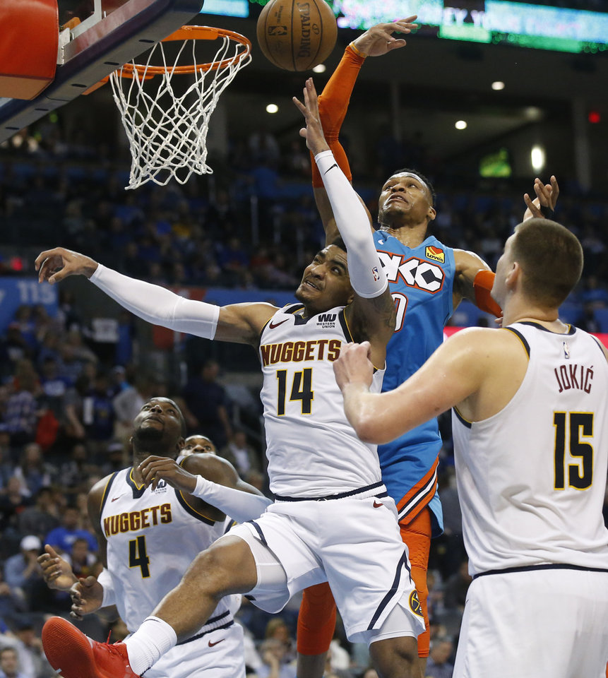 Photo - Oklahoma City Thunder guard Russell Westbrook, right, reaches for a rebound with Denver Nuggets guard Gary Harris (14) in the second half of an NBA basketball game Friday, March 29, 2019, in Oklahoma City. (AP Photo/Sue Ogrocki)