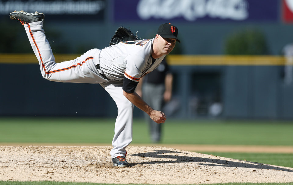 Photo - San Francisco Giants starting pitcher Tim Hudson works against the Colorado Rockies in the first inning of a baseball game in Denver on Monday, Sept. 1, 2014. (AP Photo/David Zalubowski)