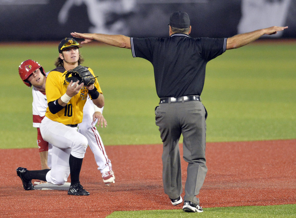 Photo - Louisville's Nick Solak, left, and Kennesaw State's Kal Simmons look at second base umpire Bill Haze to see the call, in the seventh inning of an NCAA college baseball tournament super regional game in Louisville, Ky., Friday, June 6, 2014. Louisville won 5-3. (AP Photo/Timothy D. Easley)