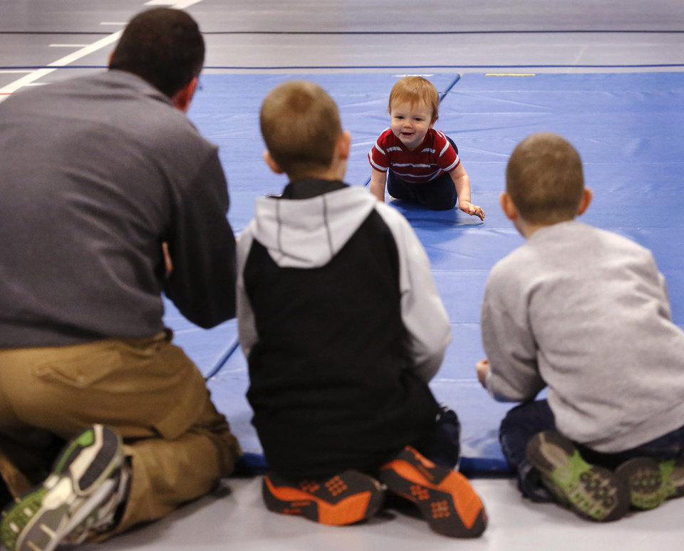 Kevin, Samuel, and Jonathan McDonell works as a team to encourage 10 month-old Caleb McDonell to hurry to the finish line. Kevin is Caleb's dad; Samuel, 9, and Jonathan, 8, are older brothers to Caleb.  Caleb's official time was 1.13 seconds.   Diaper Dash / Baby Crawl contest  at Jackie Cooper Gym in Yukon, Saturday, Jan. 5, 2013.  Organizers said nine entries registered to compete in the three categories. Age divisions were six to nine months old; 10 to14 months-old; and walking toddlers. Winner in the youngest category was Liam Sorrels, eight months. Winner of the middle category was Shiloh Meiki, 11 months, and the lone entrant in the walking toddler category was Cooper Ferrell, i year old. The contestants raced individually and were timed by judges. The babies were required to crawl  from one end to the other on a 20 foot mat. Quickest time was awarded first place.   Photo by Jim Beckel, The Oklahoman
