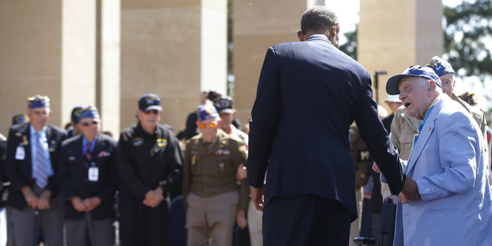 Photo - A veteran talks to U.S. President Barack Obama, at the Normandy American Cemetery, at Omaha Beach as he participates in the 70th anniversary of D-Day in Colleville sur Mer, Normandy, France, Friday, June 6, 2014. (AP Photo/Charles Dharapak)