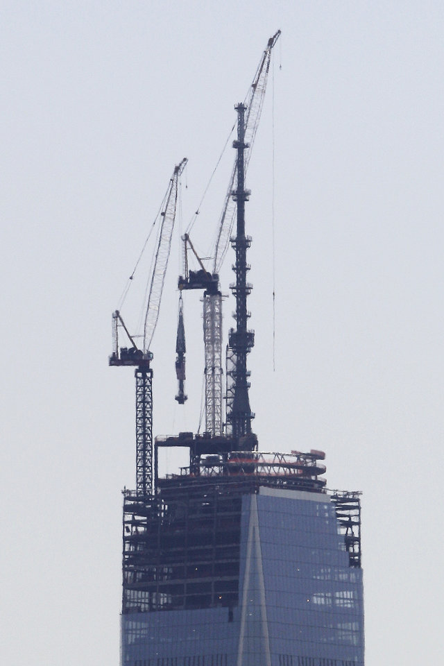 Photo - A 408-foot spire, center, is lifted toward the top of the construction of One World Trade Center seen from the Heights neighborhood of Jersey City, N.J., Thursday, May 2, 2013. The spire, which will put the building at 1,776 feet tall, will be placed on the structure at a later day. (AP Photo/Julio Cortez)