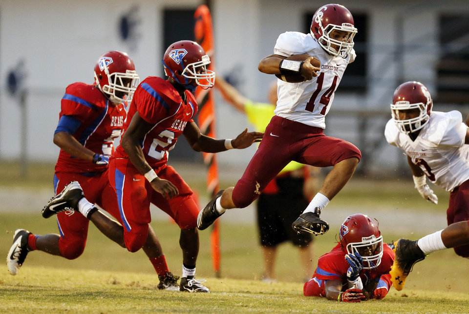 Crooked Oak's DeAndre Kenney (14) runs from John Marshall defenders during a high school football game between John Marshall and Crooked Oak at Star Spencer's Carl Twidwell Stadium, 3001 NE Spencer Rd., in Spencer, Okla., Thursday, Sept. 19, 2013. Photo by Nate Billings, The Oklahoman