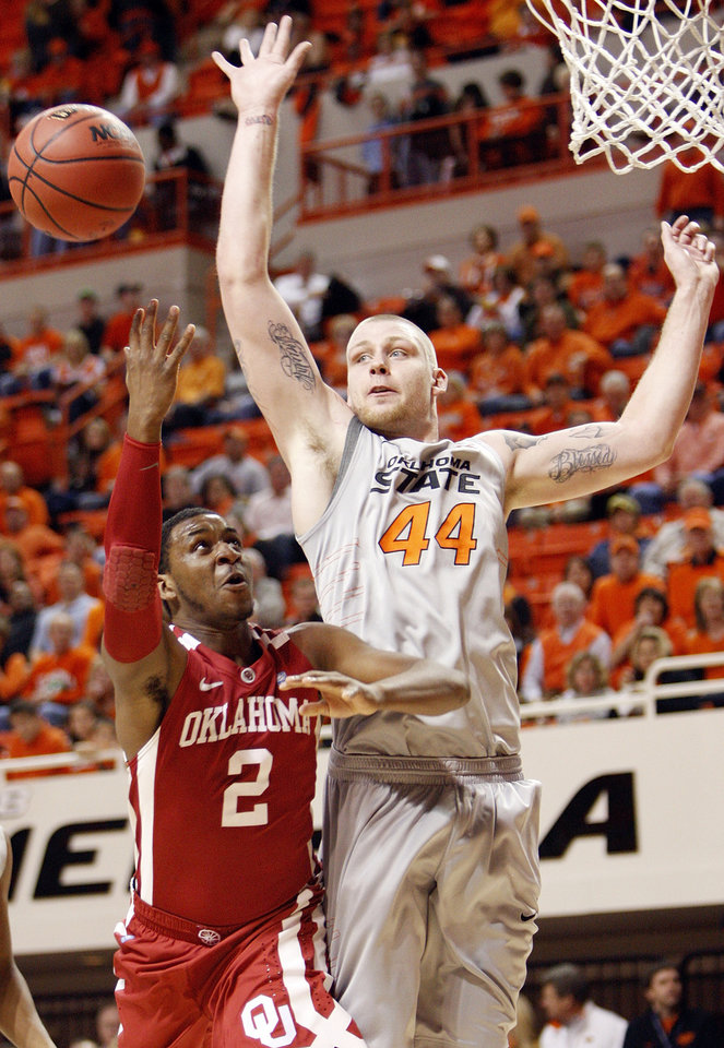 Photo - OU's Steven Pledger (2) tries to get a shot past Philip Jurick (44) of OSU in the first half during the Bedlam men's college basketball game between the Oklahoma State University Cowboys and the University of Oklahoma Sooners at Gallagher-Iba Arena in Stillwater, Okla., Monday, Jan. 9, 2012. Photo by Nate Billings, The Oklahoman