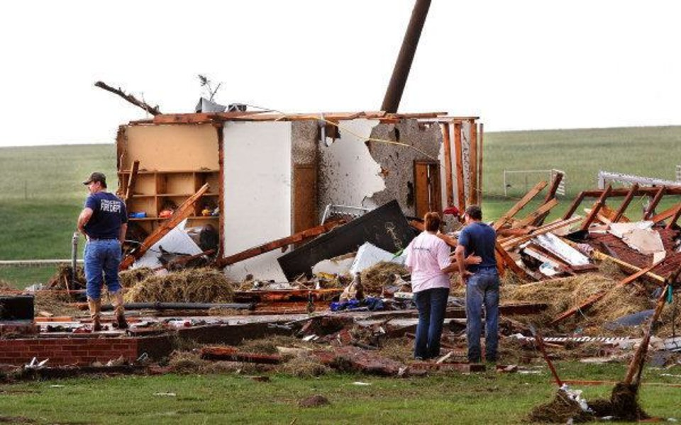 TORNADO / DAMAGE / AFTERMATH / HOUSE / STATE HIGHWAY 74: Kiley Witte, 34, far right, is comforted by a  woman as they look at what remains  of his home on SH 74 east of Cashion after a tornado destroyed it  Tuesday afternoon,  May 24, 2011,   Witte and his dog were in a storm cellar in his front yard.  His wife and young son had done to Oklahoma City and were in a safe room of a business where she works.  Photo by Jim Beckel, The Oklahoman ORG XMIT: KOD