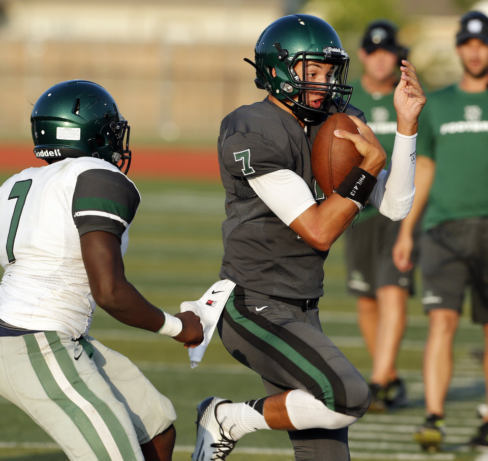 Photo - Norman North quarterback John Kolar is forced out of bounds by Edmond Santa Fe's Zeke Jenkins during a high school football scrimmage at Harve Collins Field in Norman, Okla., on Thursday, Aug. 21, 2014. Photo by Steve Sisney, The Oklahoman