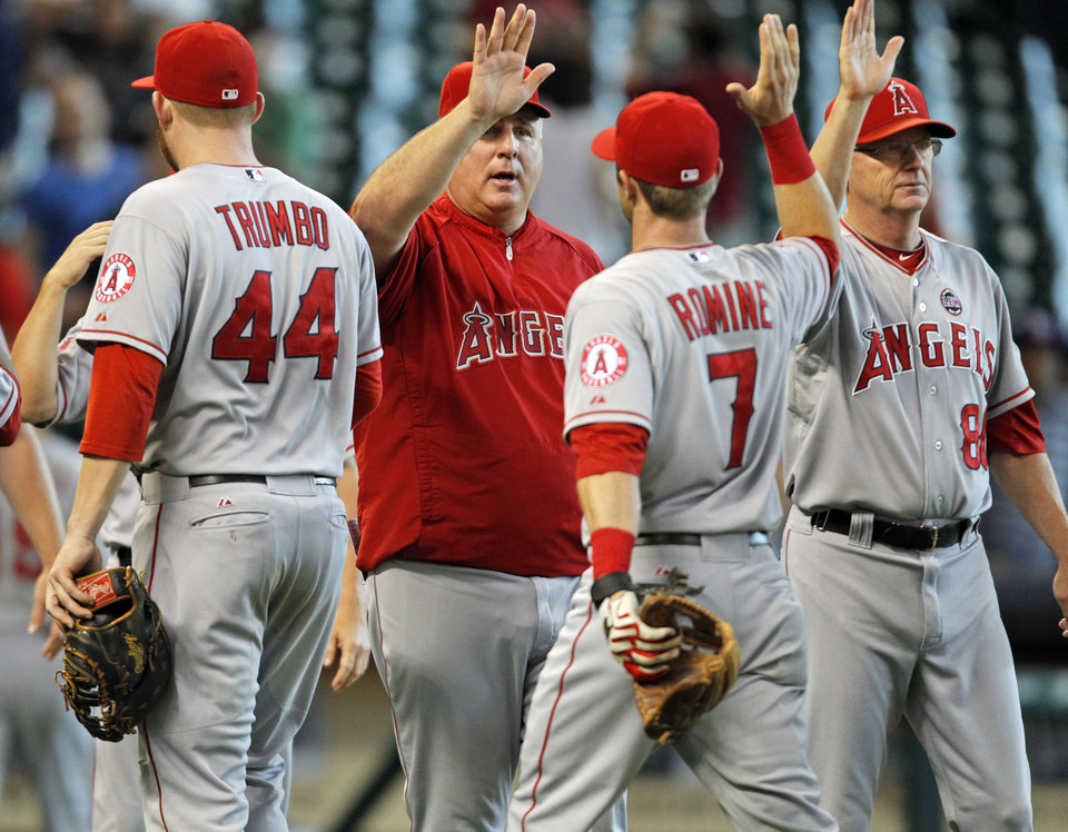 Photo - Los Angeles Angels manager Mike Scioscia, center, celebrates Andrew Romine (7) after the Angels 2-1 victory over the Houston Astros in a baseball game Sunday, Sept. 15, 2013, at Minute Maid Park in Houston. (AP Photo/Eric Christian Smith)
