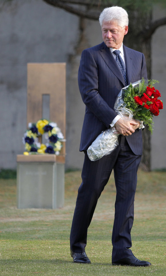 Photo - Former President Bill Clinton carries flowers as he visits the Oklahoma City National Memorial & Museum in Oklahoma City, Wednesday, April 21, 2010. Clinton is in town to receive the Reflections of Hope Award for his work in Oklahoma City after the bombing of the Alfred P. Murrah Federal Building.  Photo by Bryan Terry, The Oklahoman
