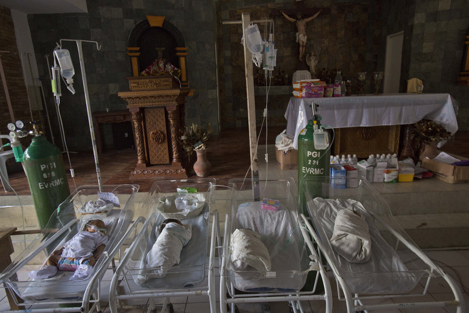 Photo - Sick and premature babies lie in cribs on the alter of a Catholic chapel inside the Eastern Visayas Regional Medical Center in Tacloban on Saturday Nov. 16, 2013. The chapel is now being used to care for infants after Typhoon Haiyan destroyed the original facility of the hospital. (AP Photo/David Guttenfelder)