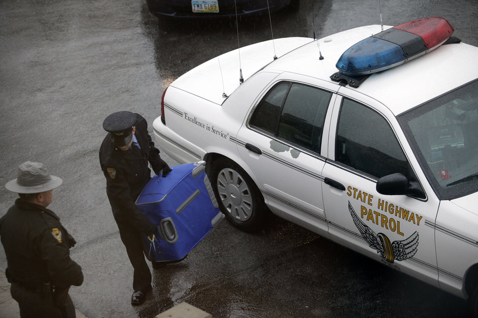 Photo -   Troopers with the Ohio Highway State Patrol deliver a suitcase, Friday, March 2, 2012, on the campus of Bowling Green State University in Bowling Green, Ohio, belonging to one of the victims of an early morning crash. A driver going the wrong way on a interstate I-75 crashed head-on into another car early Friday, killing three Bowling Green State University sorority sisters and critically injuring two others. The driver going the wron way on I-75 was also killed. (AP Photo/Sentinel-Tribune, J.D. Pooley) MANDATORY CREDIT, TOLEDO BLADE OUT