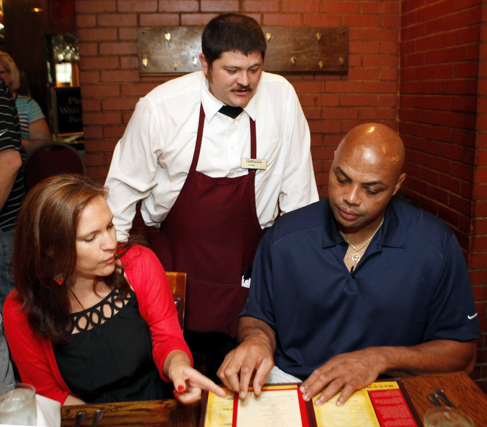Photo - Michael Sharp, a server at Cattlemen's Steakhouse, middle, discusses the menu with former NBA player and TNT analyst Charles Barkley as Elly Trickett, executive editor of weightwatchers.com, gives Barkley advice on what to order at Cattlemen's Steakhouse during a tour of Oklahoma City, Friday, June 1, 2012. Photo by Nate Billings, The Oklahoman