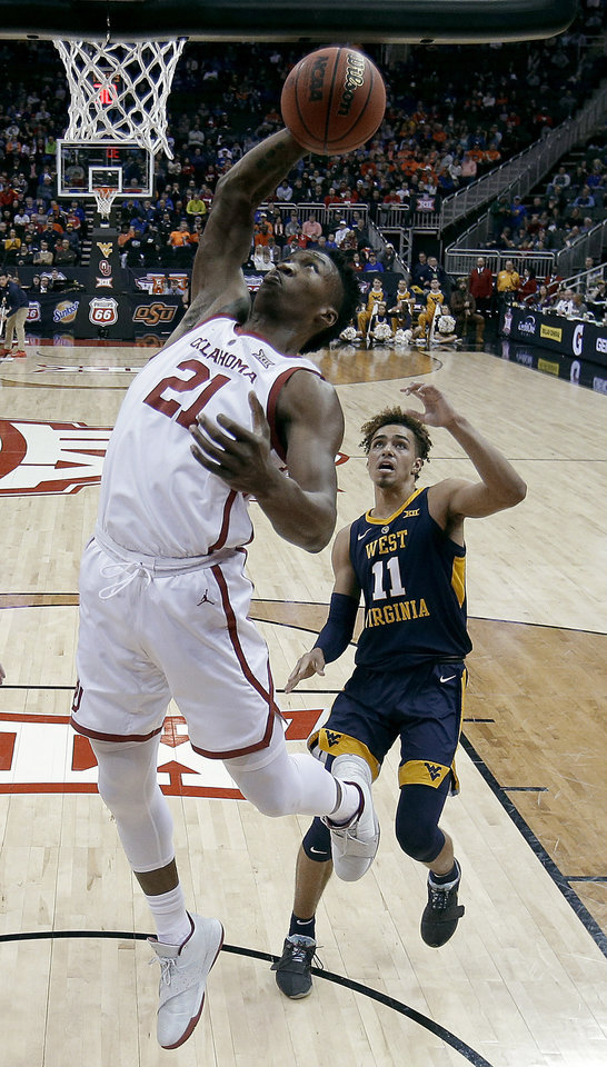 Photo - Oklahoma's Kristian Doolittle (21) beats West Virginia's Emmitt Matthews Jr. (11) to a rebound during the first half of an NCAA college basketball game in the Big 12 men's tournament Wednesday, March 13, 2019, in Kansas City, Mo. (AP Photo/Charlie Riedel)