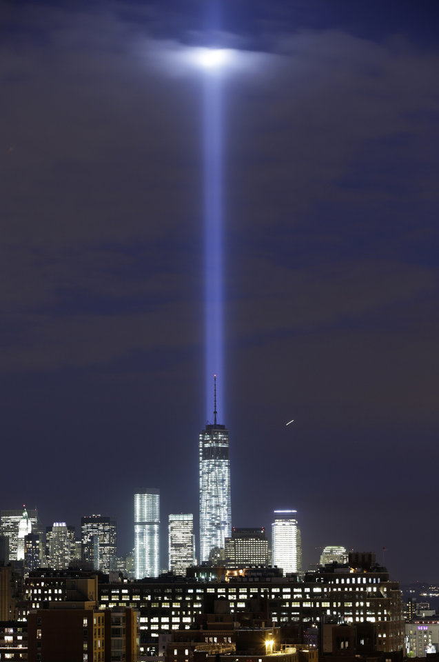 Photo - In this photo made with a long exposure, a test of the twin beams of the Tribute in Light intersect with still-under construction Tower One as they rise behind the building and above lower Manhattan, Monday, Sept. 9, 2013, in New York.  The memorial, sponsored by the Municipal Art Society, will light the sky on the evening of Sept. 11, 2013, in honor of those who died in the Sept. 11, 2001, terror attacks on the United States. (AP Photo/Kathy Willens)