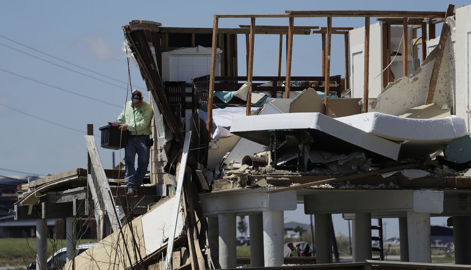 Photo - Shane Johnson removes items from a family home destroyed in the wake of Harvey, Tuesday, Aug. 29, 2017, in Rockport, Texas. (AP Photo/Eric Gay)