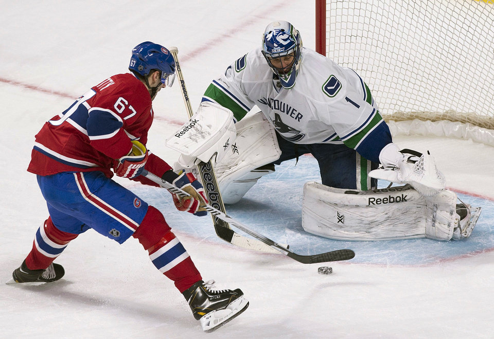 Photo - Vancouver Canucks goaltender Roberto Luongo stops a penalty shot by Montreal Canadiens' Max Pacioretty during the second period of an NHL hockey game Thursday, Feb. 6, 2014, in Montreal. (AP Photo/The Canadian Press, Graham Hughes)