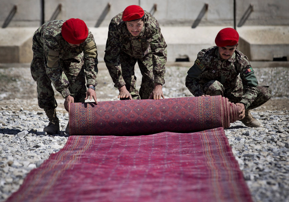 Photo - Afghan National Army soldiers roll up the red carpet after the hand over ceremony of the Parwan Detention Facility from U.S. military control to Afghan authorities in Bagram, outside Kabul, Afghanistan, Monday, March 25, 2013. The handover of Parwan Detention Facility ends a bitter chapter in American relations with Afghanistan's mercurial president, Hamid Karzai, who demanded control of the prison as a matter of national sovereignty. (AP Photo/Anja Niedringhaus)