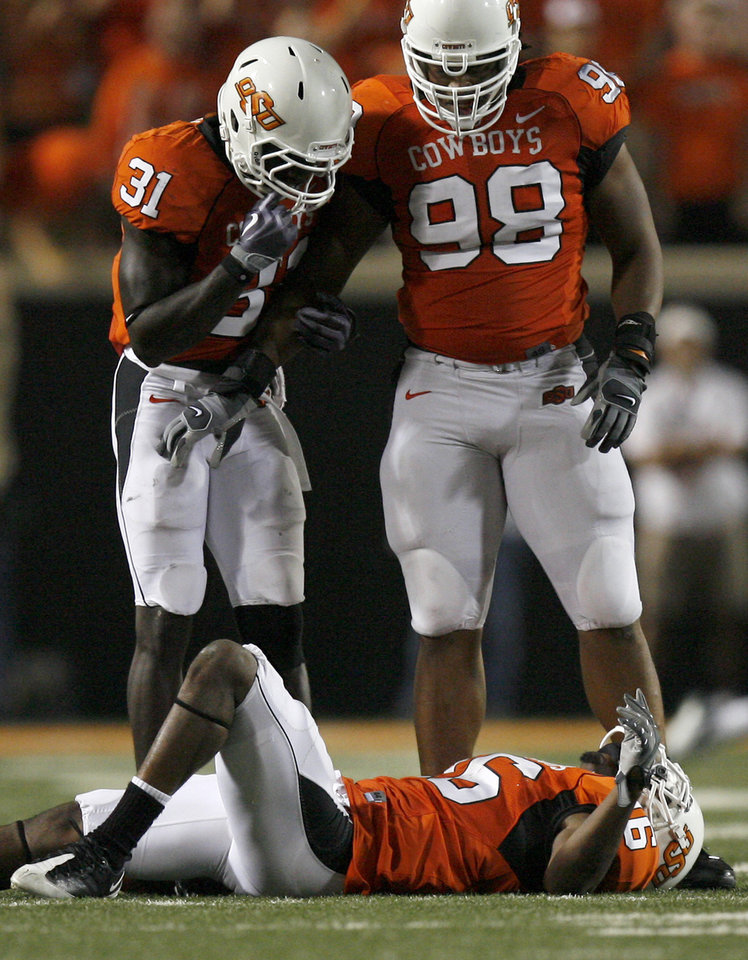 Photo - OSU's Lucien Antoine (31) and Derek Burton (98) look over an injured Perrish Cox (16) at the college football game between Oklahoma State University (OSU) and Rice University at Boone Pickens Stadium in Stillwater, Okla., Saturday, Sept. 19, 2009. Photo by Sarah Phipps, The Oklahoman ORG XMIT: KOD