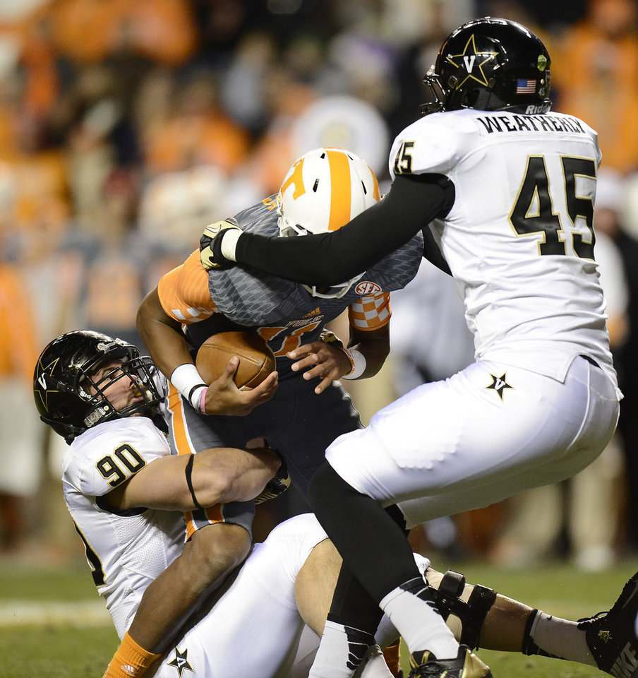 Photo - Vanderbilt defensive end Walker May (90) and Vanderbilt defensive end Stephen Weatherly (45) sack Tennessee quarterback Joshua Dobbs in the first quarter of an NCAA college football game on Saturday, Nov. 23, 2013, in Knoxville, Tenn. (AP Photo/Mark Zaleski)