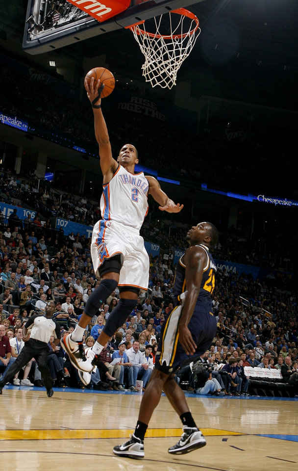 Photo - Oklahoma City's Thabo Sefolosha shoots a lay up in front of Utah's Paul Millsap during the NBA basketball game between the Oklahoma City Thunder and Utah Jazz in the Oklahoma City Arena on Sunday, Oct. 31, 2010. Photo by Sarah Phipps, The Oklahoman