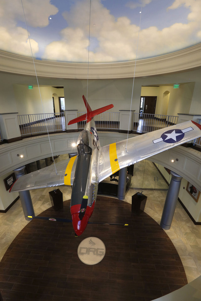 Photo -  A replica World War II P-51 Mustang fighter plane hangs in the atrium of Delaware Resource Group's new headquarters in Oklahoma City. It was placed there to honor the Tuskegee Airmen. [PHOTO BY PAUL HELLSTERN, THE OKLAHOMAN]