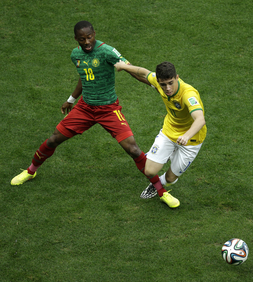 Photo - Brazil's Oscar is tacked by Cameroon's Eyong Enoh during the group A World Cup soccer match between Cameroon and Brazil at the Estadio Nacional in Brasilia, Brazil, Monday, June 23, 2014. (AP Photo/Christophe Ena)