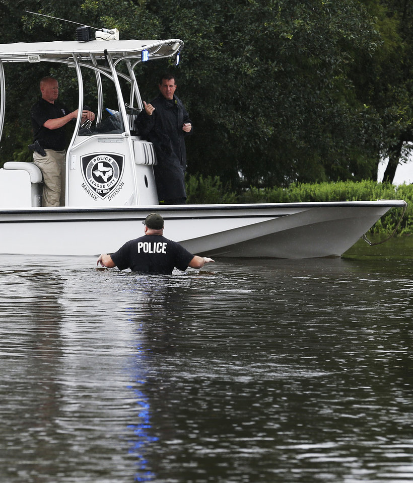 Photo - A police boat searches for residents in need of rescue along Clear Creek in League City, Texas, Sunday, Aug. 27, 2017. (Kevin M. Cox/The Galveston County Daily News via AP)
