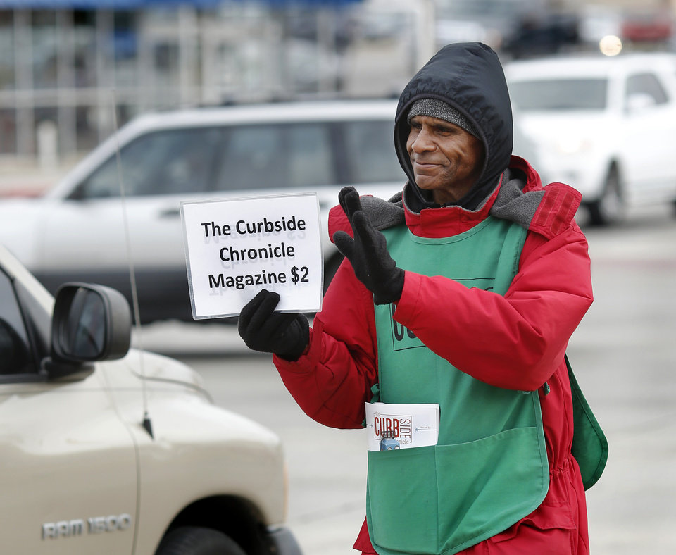 Photo - Frank Gibbs walks up and down the northwest corner of NW 23 and Broadway Tuesday afternoon, Nov. 7, 2017, trying to attract the attention and, hopefully, a few dollars from drivers who pass him at this busy intersection while he sells copies of the Curbside Chronicle, a magazine published by the Homeless Alliance. Gibbs said he follows current laws regarding soliciting funds at city intersections. He explained he sells from the sidewalk nearest the street, and was emphatic in the fact he
