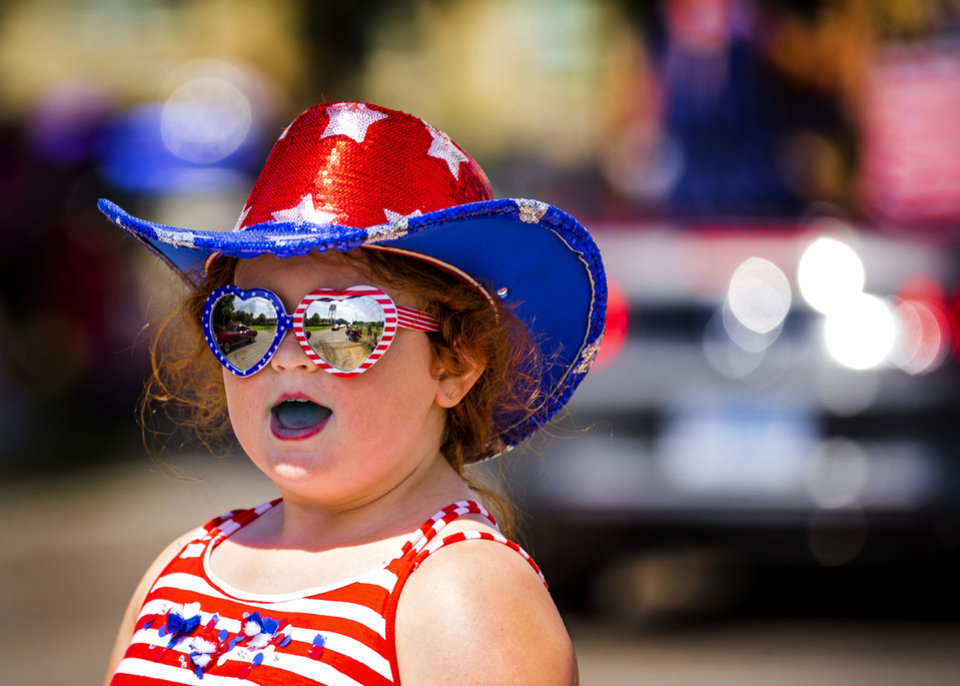 Photo - Megan Hull, 8, dressed for the occasion as she takes in the sights of those taking part in the Bethany Freedom Festival parade in Bethany, Okla. on Thursday, July 4, 2019.    [Chris Landsberger/The Oklahoman]