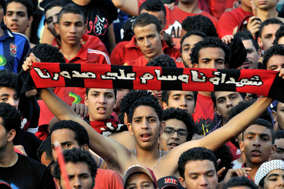 Photo - An Egyptian club Al Ahly fan holds a scarf with Arabic translation that reads,