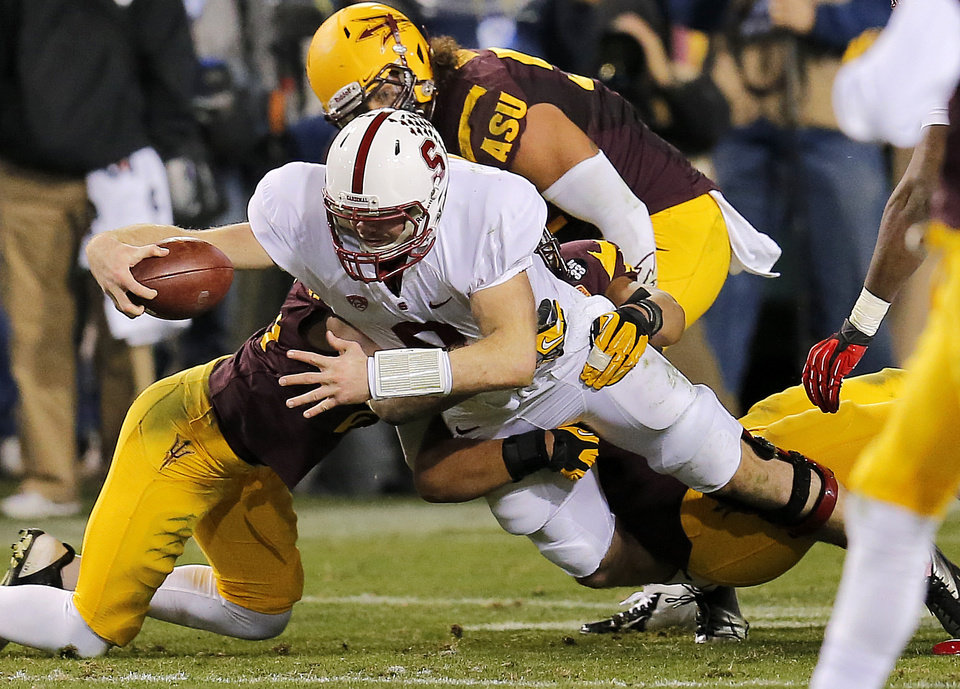 Stanford quarterback Kevin Hogan dives for a first down as he his pulled down by Arizona State defenders during the first half of the  NCAA Pac-12 Championship football game, Saturday, Dec. 7, 2013, in Tempe, Ariz. (AP Photo/Matt York)