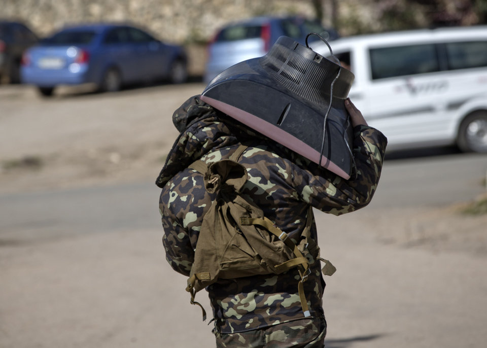 Photo - A Ukrainian airman carries a TV set as he leaves the Belbek air base, outside Sevastopol, Crimea, Friday, March 21, 2014. The base commander Col. Yuliy Mamchur said he was asked by the Russian military to turn over the base but is unwilling to do so until he receives orders from the Ukrainian defense ministry. (AP Photo/Vadim Ghirda)