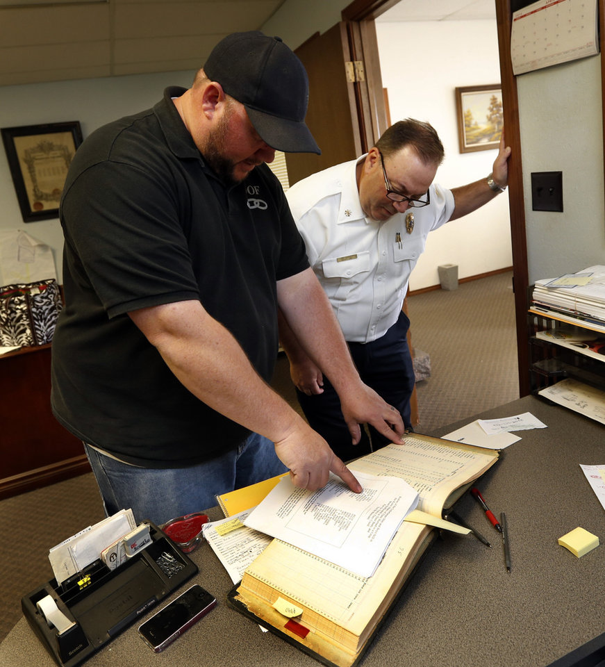 Photo -  IOOF Cemetery manager Tim Bowling, left, and Deputy Fire Chief Jim Bailey look up the names of the dead buried the day after a fire on April 13, 1918, killed 40 patients at the state hospital for the mentally ill.   STEVE SISNEY -