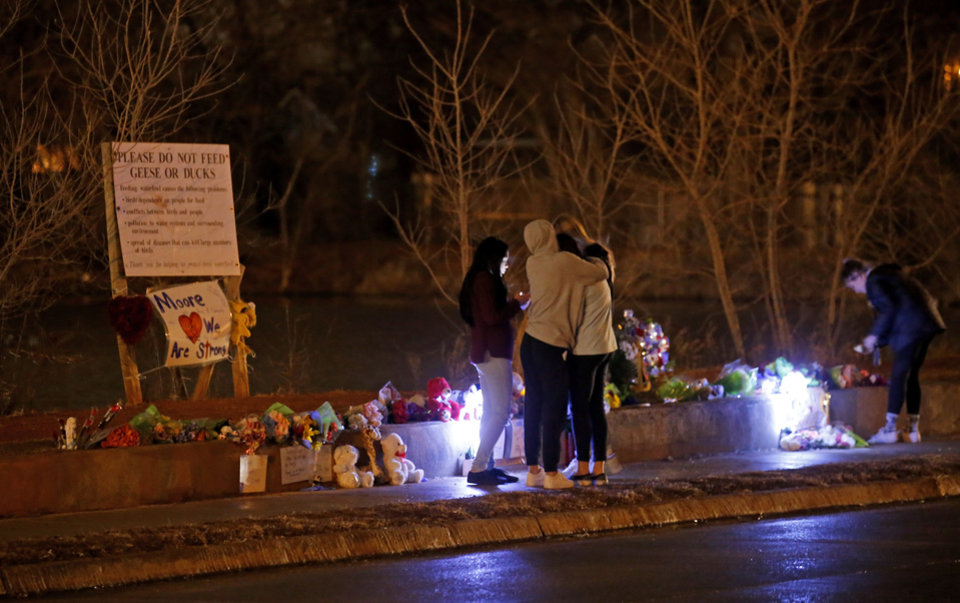 Photo -  People gather around at the site of Monday's fatal crash in Moore that claimed the lives of two students and injured four others. [Sarah Phipps/The Oklahoman]