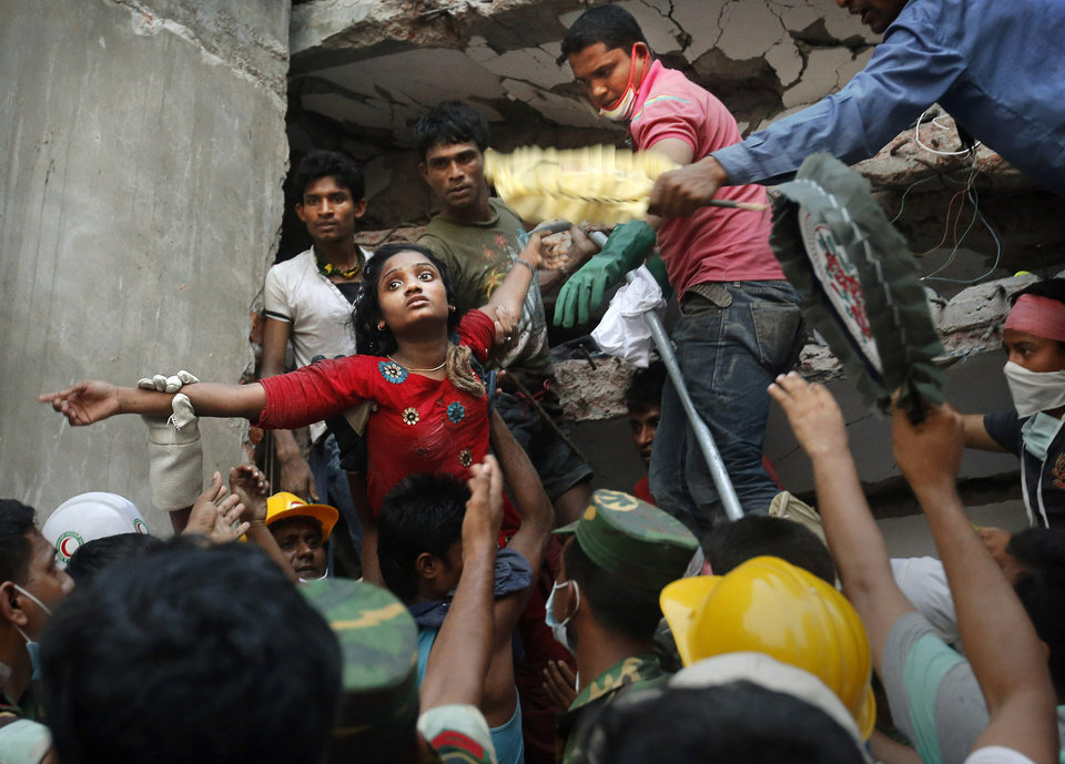 A Bangladeshi woman survivor is lifted out of the rubble by rescuers at the site of a building that collapsed Wednesday in Savar, near Dhaka, Bangladesh, Thursday, April 25, 2013. By Thursday, the death toll reached at least 194 people as rescuers continued to search for injured and missing, after a huge section of an eight-story building that housed several garment factories splintered into a pile of concrete.(AP Photo/Kevin Frayer)
