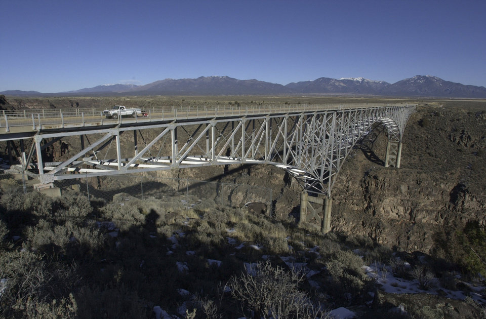 Photo - FILE - This Dec. 9, 2006 file photo shows The Rio Grande Gorge Bridge near Taos N.M. One of the nation's highest and most famous bridges, this steel deck arch bridge spans one of New Mexico's most scenic vistas. Located about 10 miles northwest of Taos along U.S. 64 the bridge sits 565 feet above New Mexico's mini Grand Canyon, making it the seventh largest bridge in the world. (AP Photo/Mike Stewart, File)