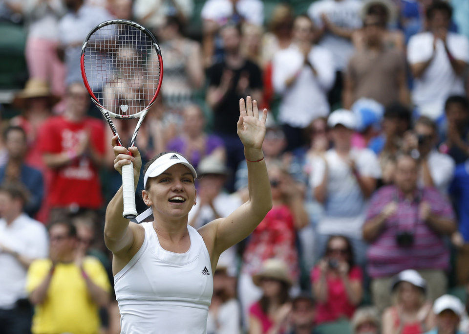 Photo - Simona Halep of Romania reacts to the applause of the crowd after defeating Sabine Lisicki of Germany in their women's singles quarterfinal match at the All England Lawn Tennis Championships in Wimbledon, London, Wednesday, July 2, 2014. (AP Photo/Pavel Golovkin)