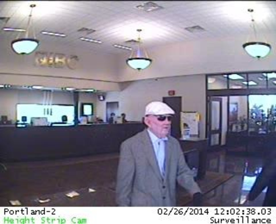 Photo -  Surveillance photo a bank robbery suspect. The man was described as being about 5 feet 7 inches to 5 feet 9 inches tall, of medium build and wearing a mask depicting an older white man. Photo provided by the FBI    -  Provided by the FBI