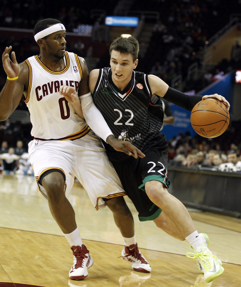 Photo -   Montepaschi Siena's Matt Janning (22) drives past Cleveland Cavaliers' C.J. Miles in the first quarter of a preseason NBA basketball game, Monday, Oct. 8, 2012, in Cleveland. (AP Photo/Tony Dejak)