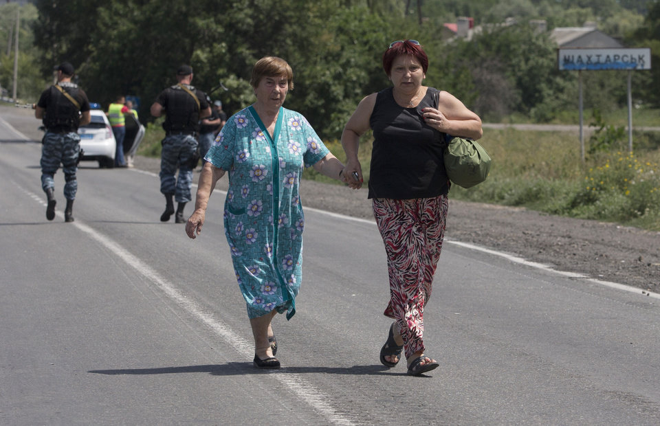 Photo - Self-proclamed Donetsk People's Republic policemen watch refugees fleeing  Shakhtarsk, Donetsk region, eastern Ukraine on Monday, July 28, 2014. An international police team abandoned its attempt to reach the crash site of a Malaysia Airlines plane for a second day running Monday as clashes raged in a town on the road to the area.(AP Photo/Dmitry Lovetsky)