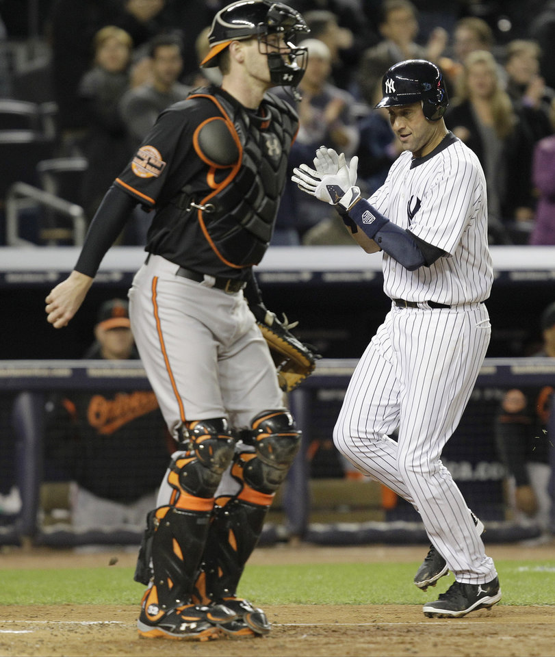 Photo -   New York Yankees' Derek Jeter, right, claps as he runs past Baltimore Orioles catcher Matt Wieters to score on an double by Ichiro Suzuki during the sixth inning of Game 5 of the American League division baseball series, Friday, Oct. 12, 2012, in New York. (AP Photo/Kathy Willens)