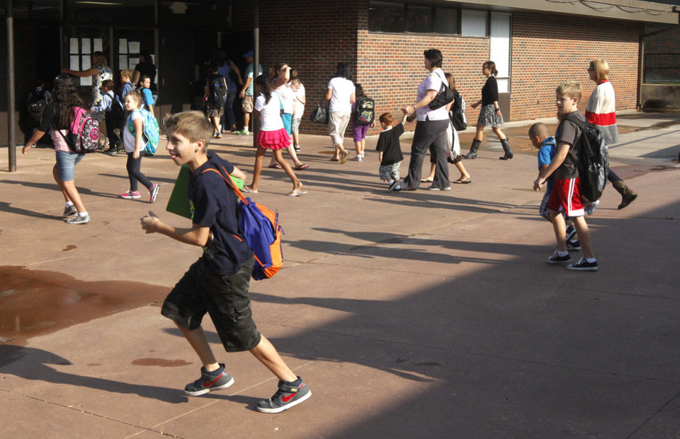 Photo - Children run to their classrooms as Plaza Towers Elementary School students begin their first day of classes Friday in their temporary location at Central Junior High in Moore.  Photo by Paul Hellstern, The Oklahoman  PAUL HELLSTERN - Oklahoman