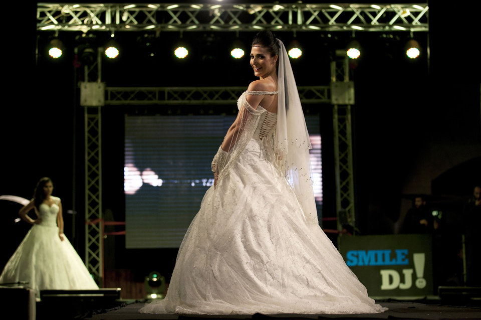 Photo - In this photo taken Friday, May 2, 2014, a model displays a creation by designer Fayzeh Pearl during the Palestine Fashion Week 2014, in the West Bank city of Ramallah. Pearl showed off more traditional designs, including beaded wedding dresses and colorful formal attire. (AP Photo/Nasser Nasser)