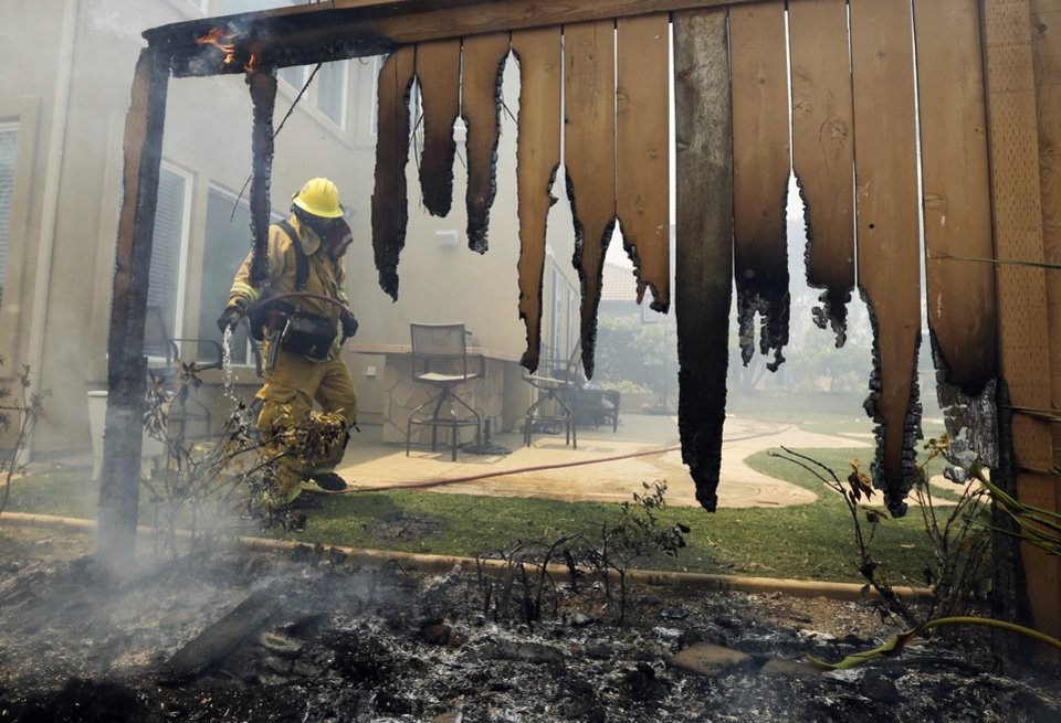 Photo - A Firefighter puts water on a house fence during a wildfire Wednesday, May 14, 2014, in Carlsbad, Calif. More wildfires broke out Wednesday in San Diego County — threatening homes in Carlsbad and forcing the evacuations of military housing and an elementary school at Camp Pendleton — as Southern California is in the grip of a heat wave. (AP Photo)