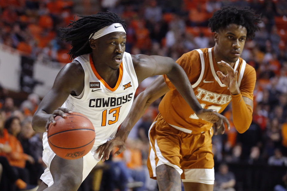 Photo - Oklahoma State's Cameron McGriff (12) goes past Texas' Jase Febres (13) during an NCAA basketball game between the Oklahoma State University Cowboys (OSU) and the Texas Longhorns at Gallagher-Iba Arena in Stillwater, Okla., Wednesday, Jan. 15, 2020. Oklahoma State lost 76-64. [Bryan Terry/The Oklahoman]