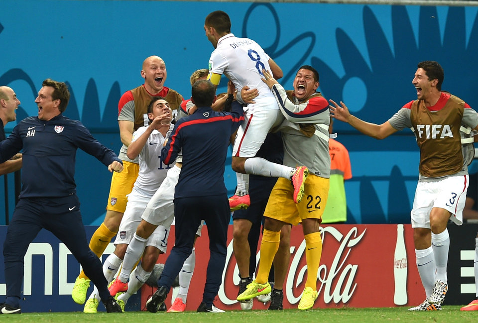 Photo - United States' Clint Dempsey celebrates with his teammates after scoring his side's second goal during the group G World Cup soccer match between the USA and Portugal at the Arena da Amazonia in Manaus, Brazil, Sunday, June 22, 2014. (AP Photo/Paulo Duarte)