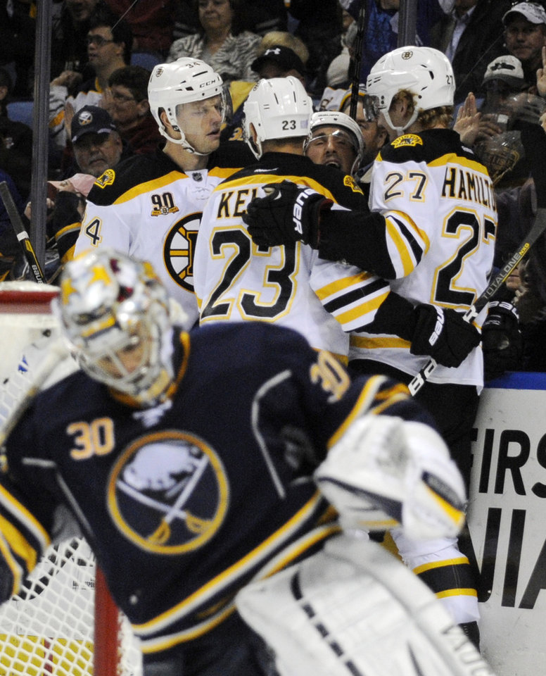 Photo - Buffalo Sabres'  Ryan Miller (30) reacts after a goal by Boston Bruins' Dougie Hamilton (27) who celebrates with Carl Soderberg (34), Chris Kelly (23), and Brad Marchand (63) during the second period of an NHL hockey game in Buffalo, N.Y., Wednesday, Oct. 23, 2013. Boston won 5-2.  (AP Photo/Gary Wiepert)