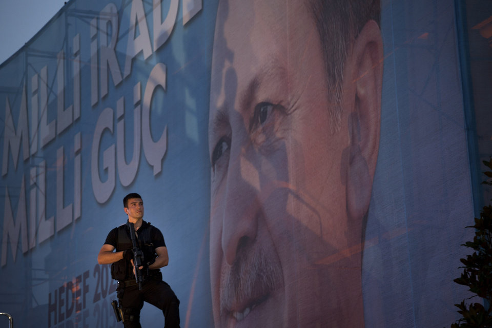 Photo - A member of security watches as the Prime Minister Recep Tayyip Erdogan talks to the crowd in downtown Istanbul, Turkey, on Sunday, Aug. 10, 2014. Turks were voting in their first direct presidential election Sunday _ a watershed event in Turkey's 91-year history, where the president was previously elected by Parliament. Prime Minister RecepTayyip Erdogan, who has dominated the country's politics for the past decade, is the strong front-runner to replace the incumbent, Abdullah Gul, for a five-year term. (AP Photo/Emilio Morenatti)