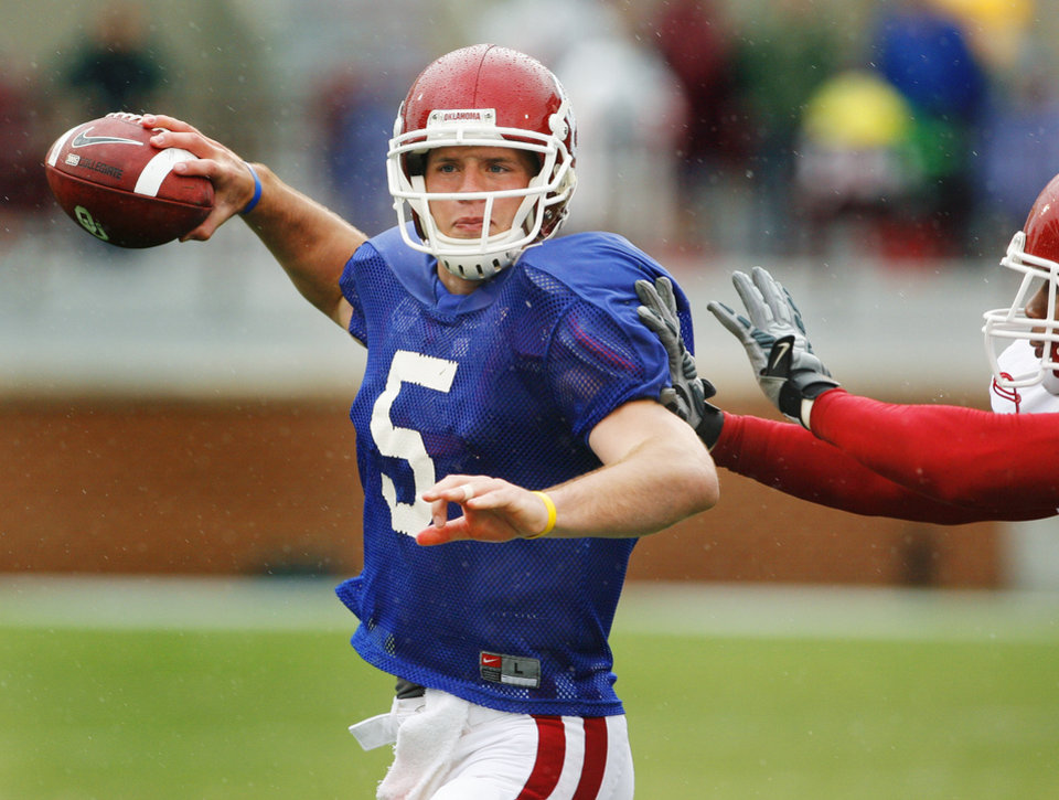 Photo - Quarterback John Nimo (5) is pressured on a throw during the spring Red and White football game for the University of Oklahoma (OU) Sooners at Gaylord Family/Oklahoma Memorial Stadium on Saturday, April 17, 2010, in Norman, Okla.  Photo by Steve Sisney, The Oklahoman