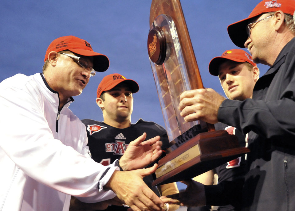 Arkansas State head coach Gus Malzahn, from left, quarterback Ryan Aplin and linebacker Nathan Herrold are presented with the Sun Belt Conference trophy following their NCAA college football game against Middle Tennessee on Saturday, Dec. 1, 2012, in Jonesboro, Ark. (AP Photo/The Jonesboro Sun, Krystin McClellan)